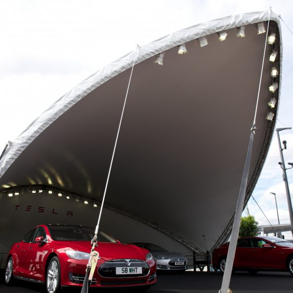 S2000 SaddleSpan Concert outdoor event structure raised on base extensions with bespoke branding for Tesla